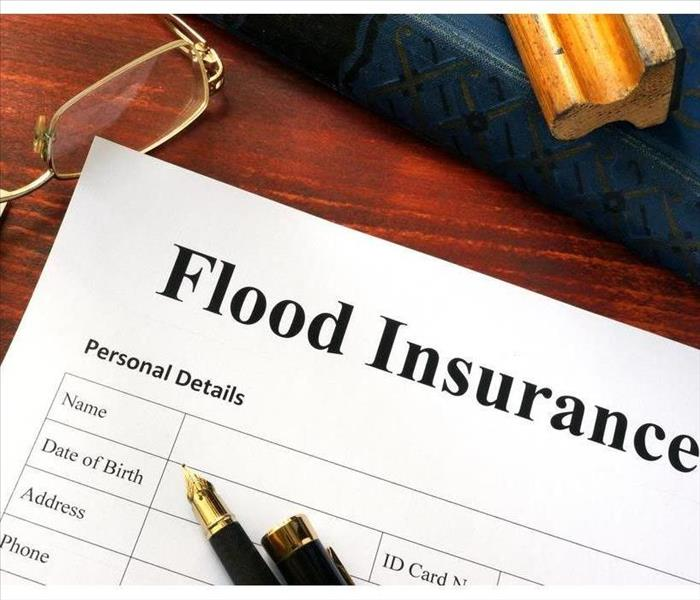 Flood insurance form on a table with a book